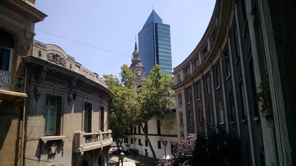 Foto com vista da arquitetura do bairro Paris-Londres em Santiago. Ao fundo, prédio comercial do centro.